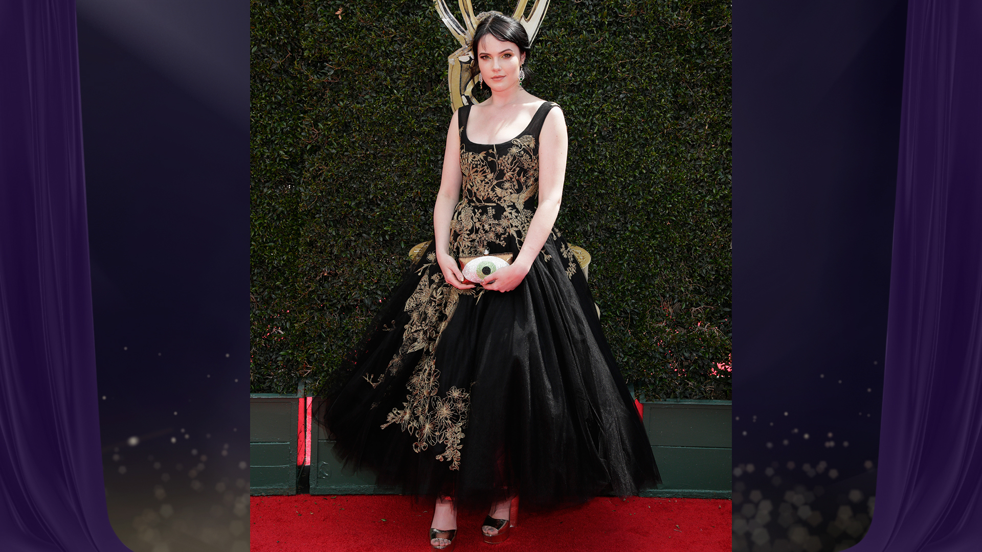 Y&R star Cait Fairbanks, who's nominated for Outstanding Younger Actress in a Drama Series, wears a black princess gown with gold floral appliqué.