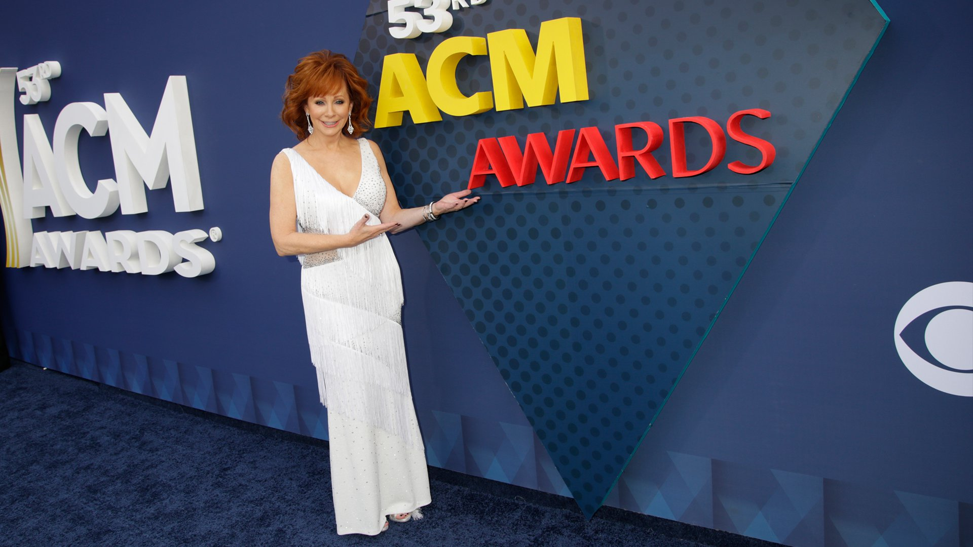 Reba McEntire manages to pose on the ACM red carpet before starting her hosting duties.