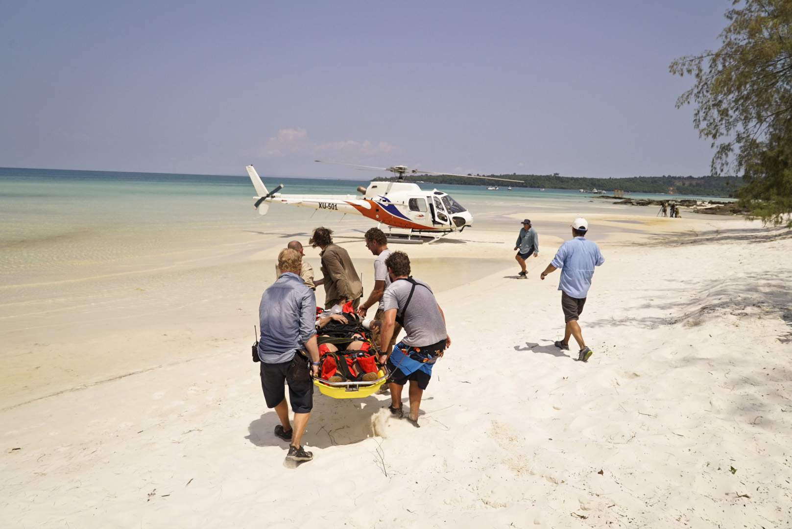 Jeff Probst guides one castaway toward a helicopter for evacuation.