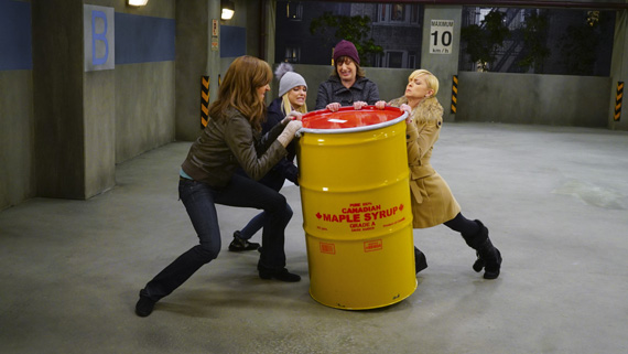 Bonnie, Christy, Wendy, and Jill struggle to lift the heavy load into the car.