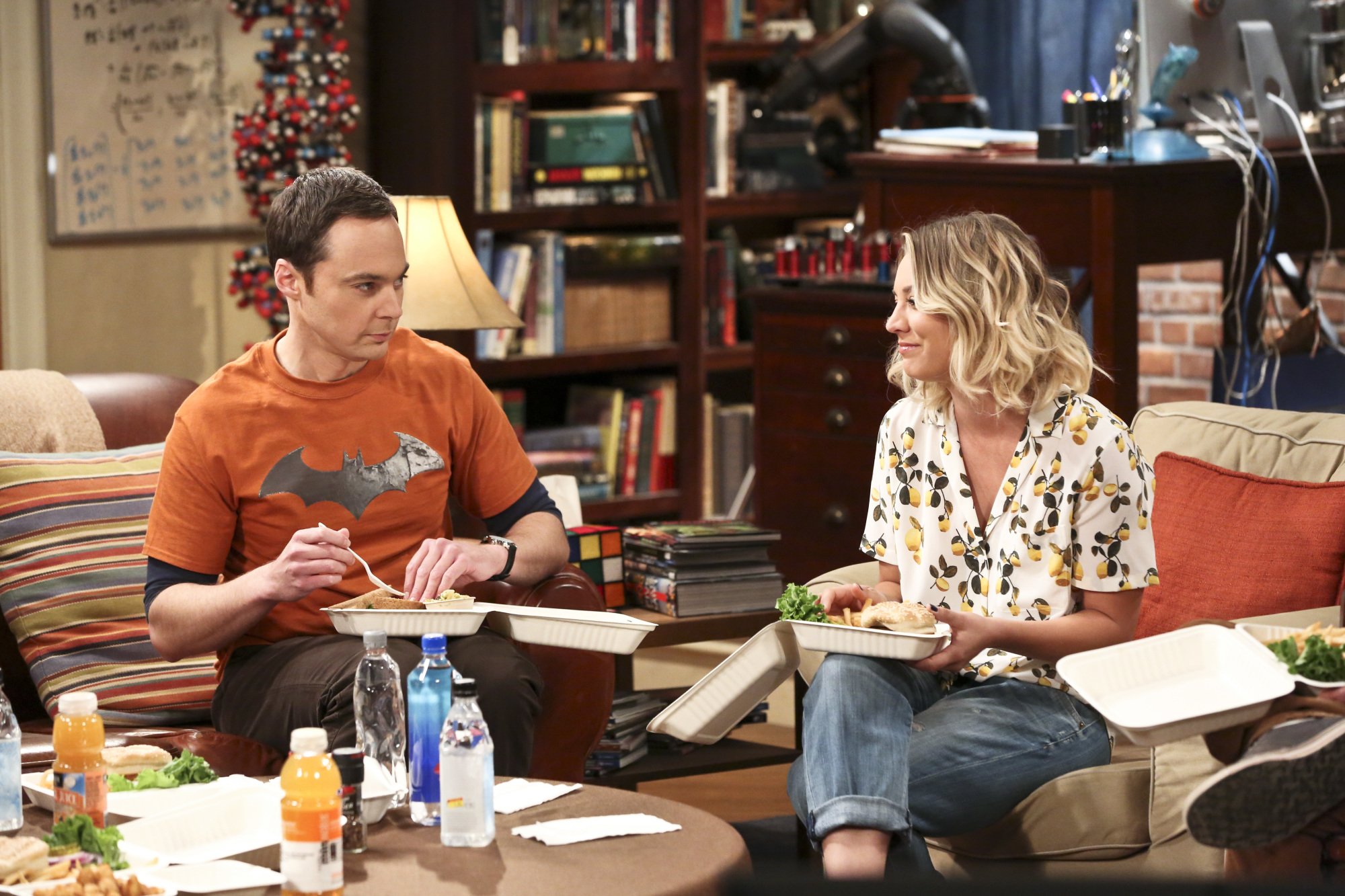 Penny chuckles at Sheldon while the gang partakes in some takeout.