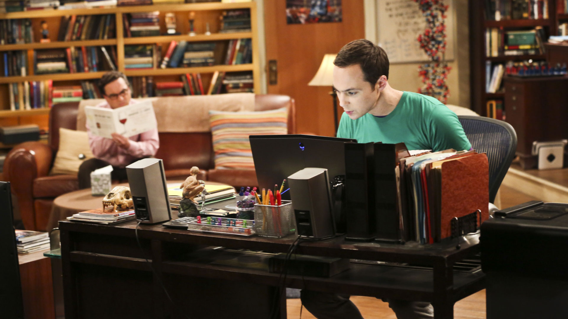 Sheldon plans an exciting evening while Leonard quietly reads on the couch.