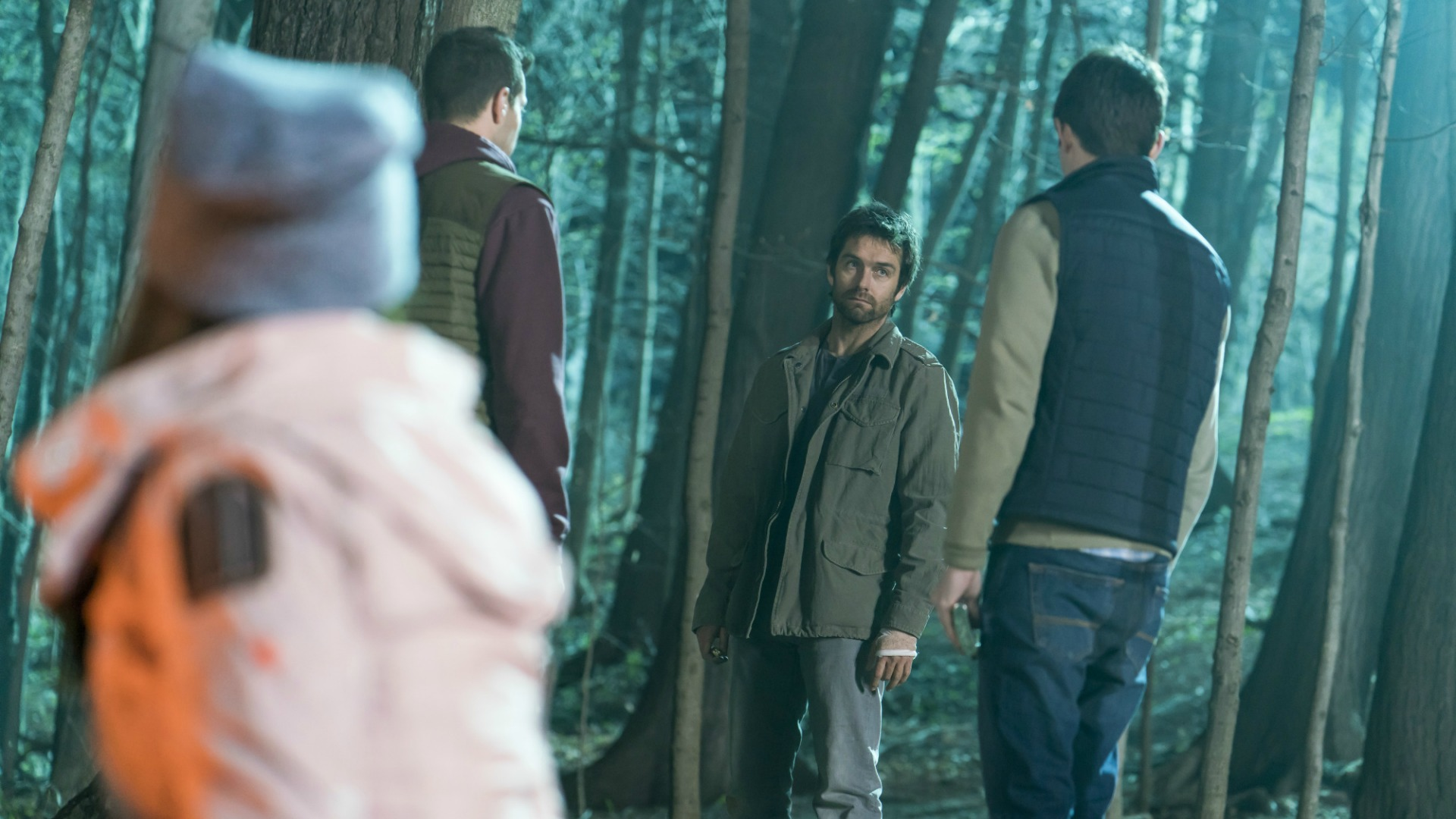 Garrett confronts a pair of young men in the woods.