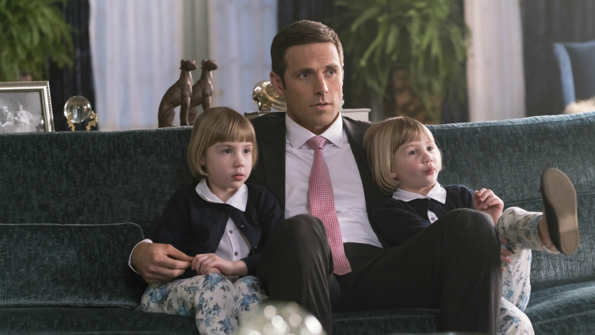 Tom sits with his twin daughters.
