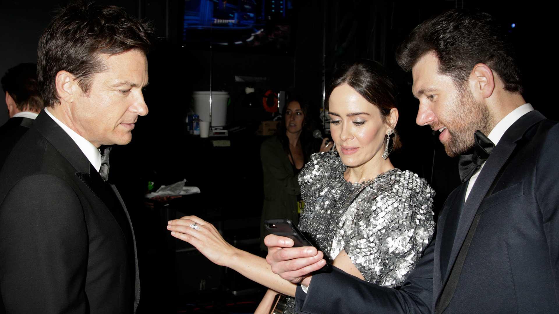 Billy Eichner shows Jason Bateman and Sarah Paulson something on his phone.