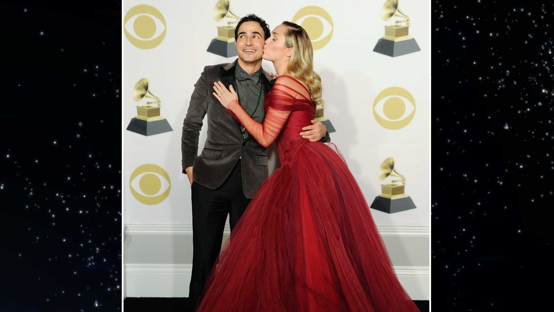 Fashion designer Zac Posen gets a kiss on the cheek from performer Miley Cyrus in the 60th Annual GRAMMY Awards press room.