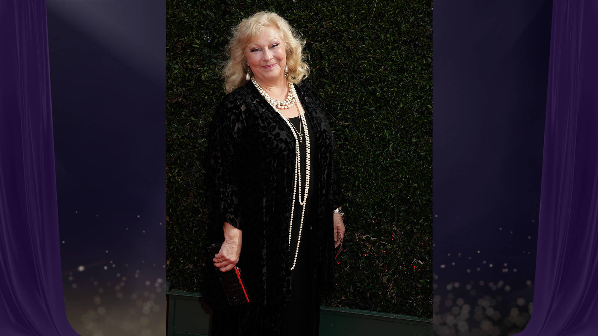 Beth Maitland from The Young and the Restless accentuates her black dress with strings and strings of pearls.