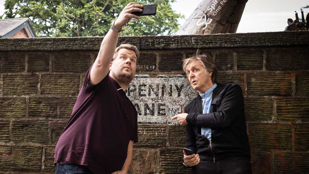 Paul McCartney and James Corden take a selfie in front of Penny Lane.