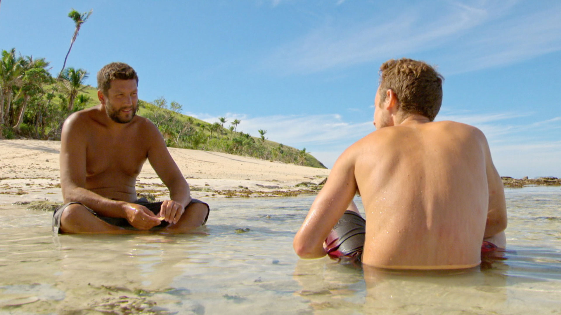 Bret sits with Adam and talks strategy on the Fiji shore.