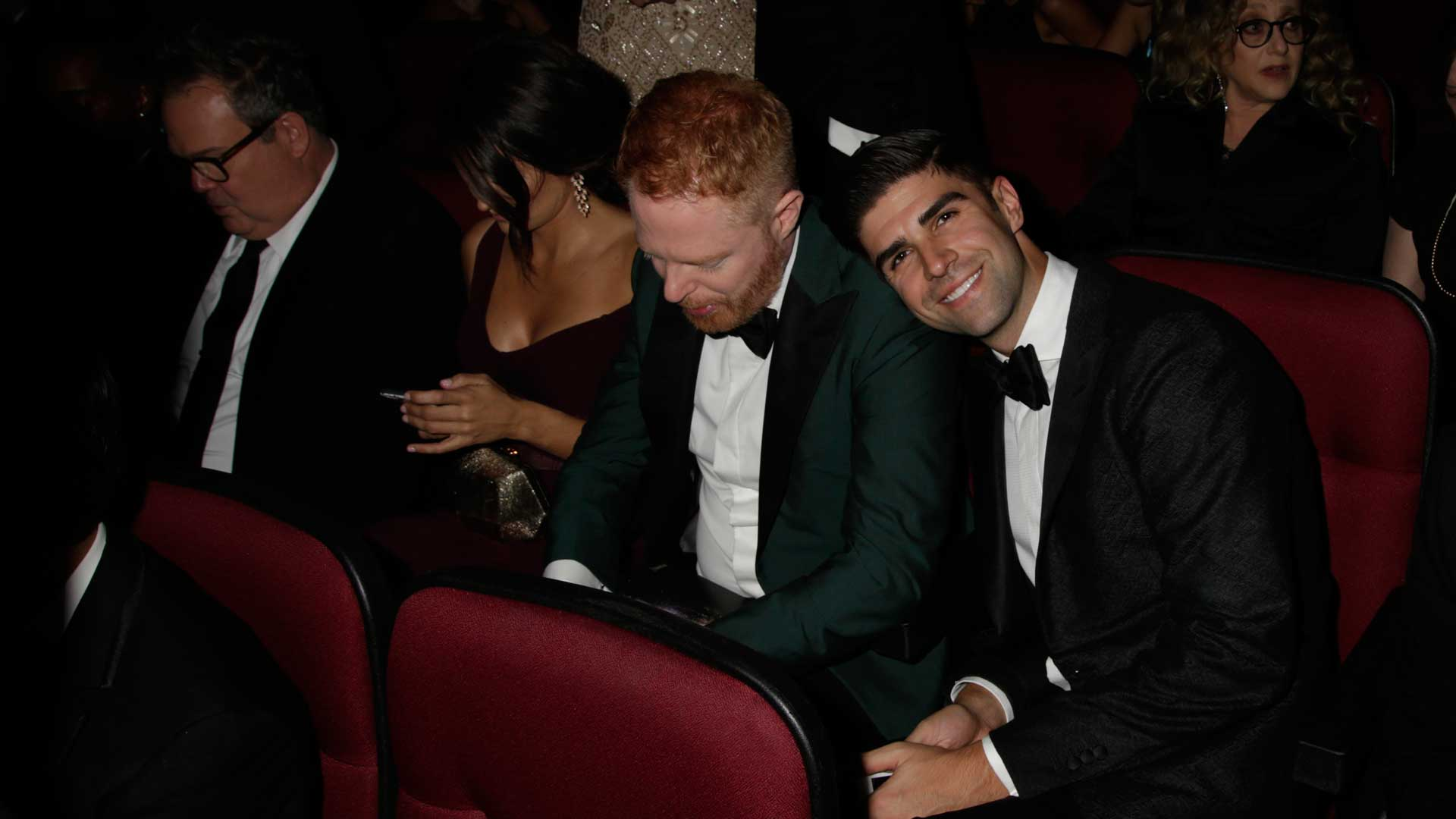 Justin Mikita puts his head on husband Jesse Tyler Ferguson's shoulder while the Modern Family actor checks his phone.