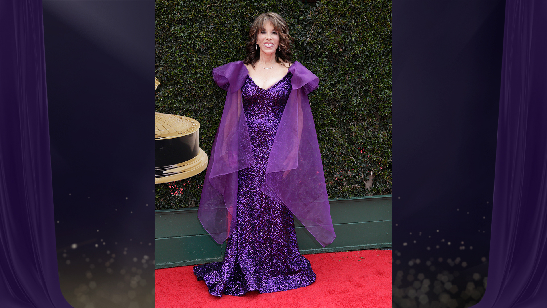 Kate Linder from The Young and the Restless sparkles in a purple sequin floor-length gown with matching violet chiffon cape.