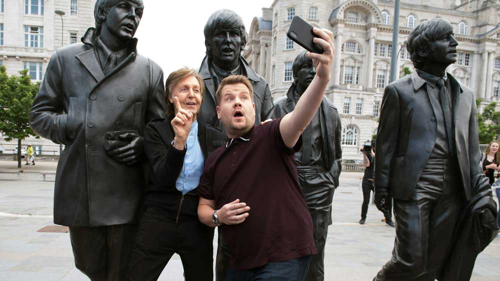 Paul McCartney and James Corden take a selfie in front of the Beatles statue in Liverpool.