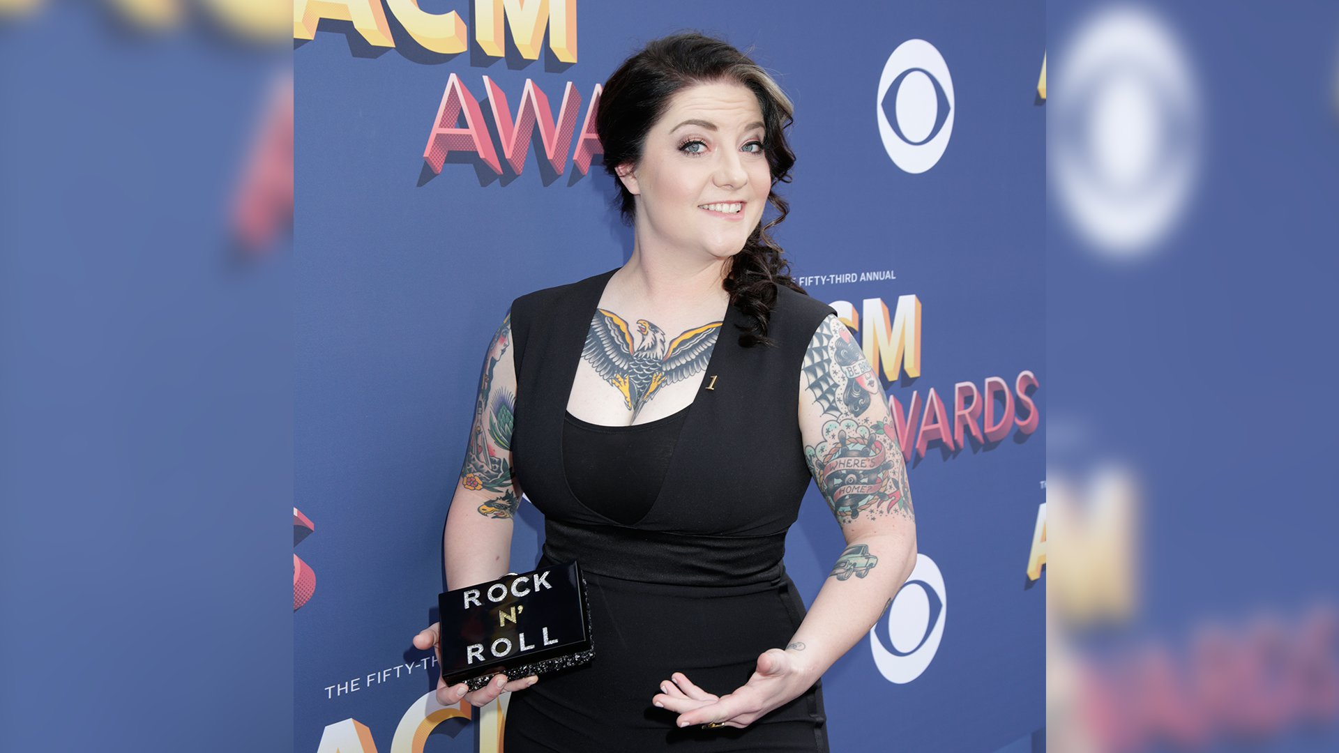Singer Ashley McBryde pairs a simple black dress with her colorful tattoos.