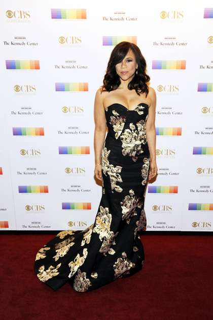 Actress Rosie Perez poses in a fitted floral gown complete with a dramatic train.