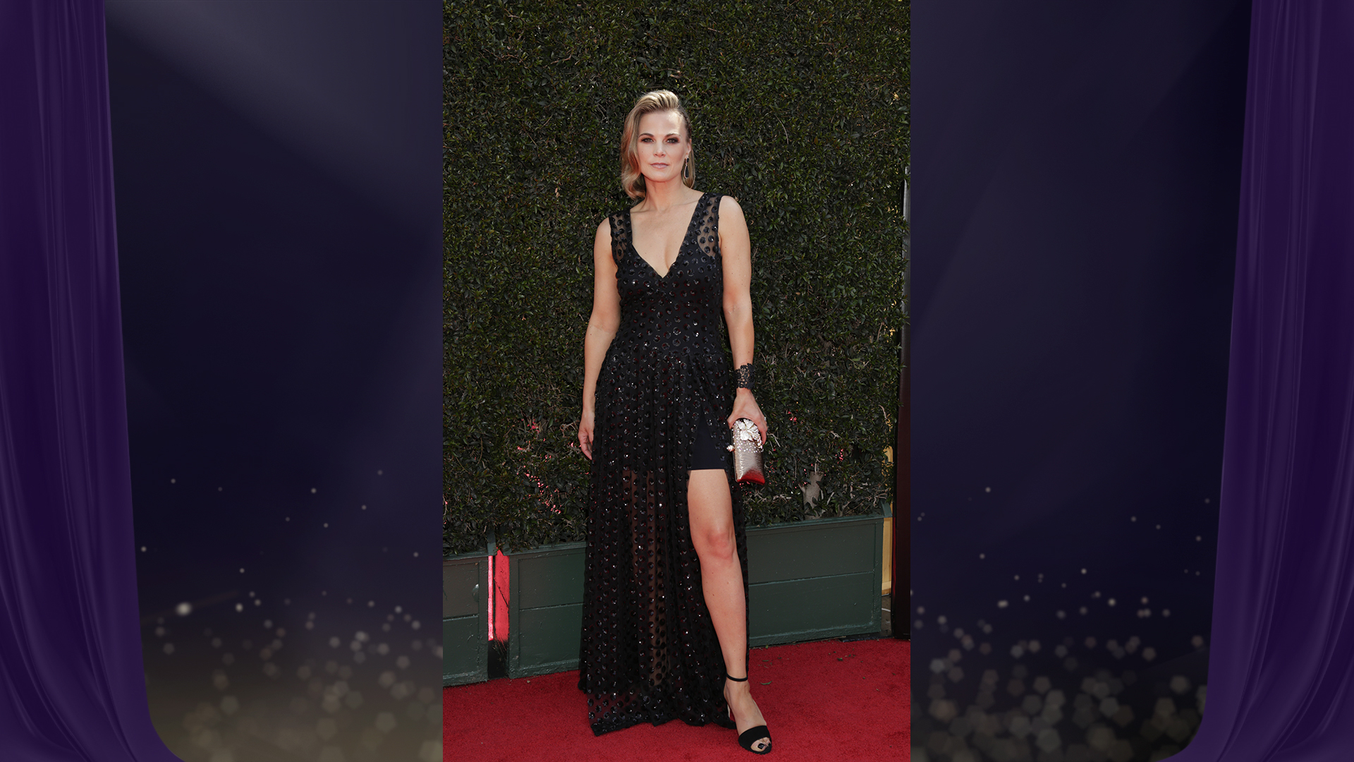 Gina Tognoni from The Young and the Restless wears a black mini dress draped in an overlay of black polka-dot chiffon.