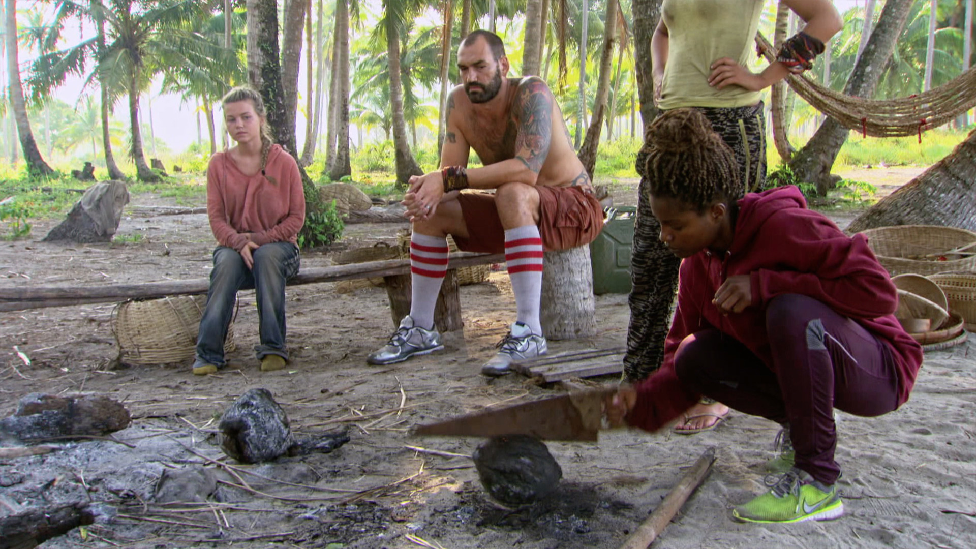 Julia and Scot watch Cydney as she cracks open a coconut.