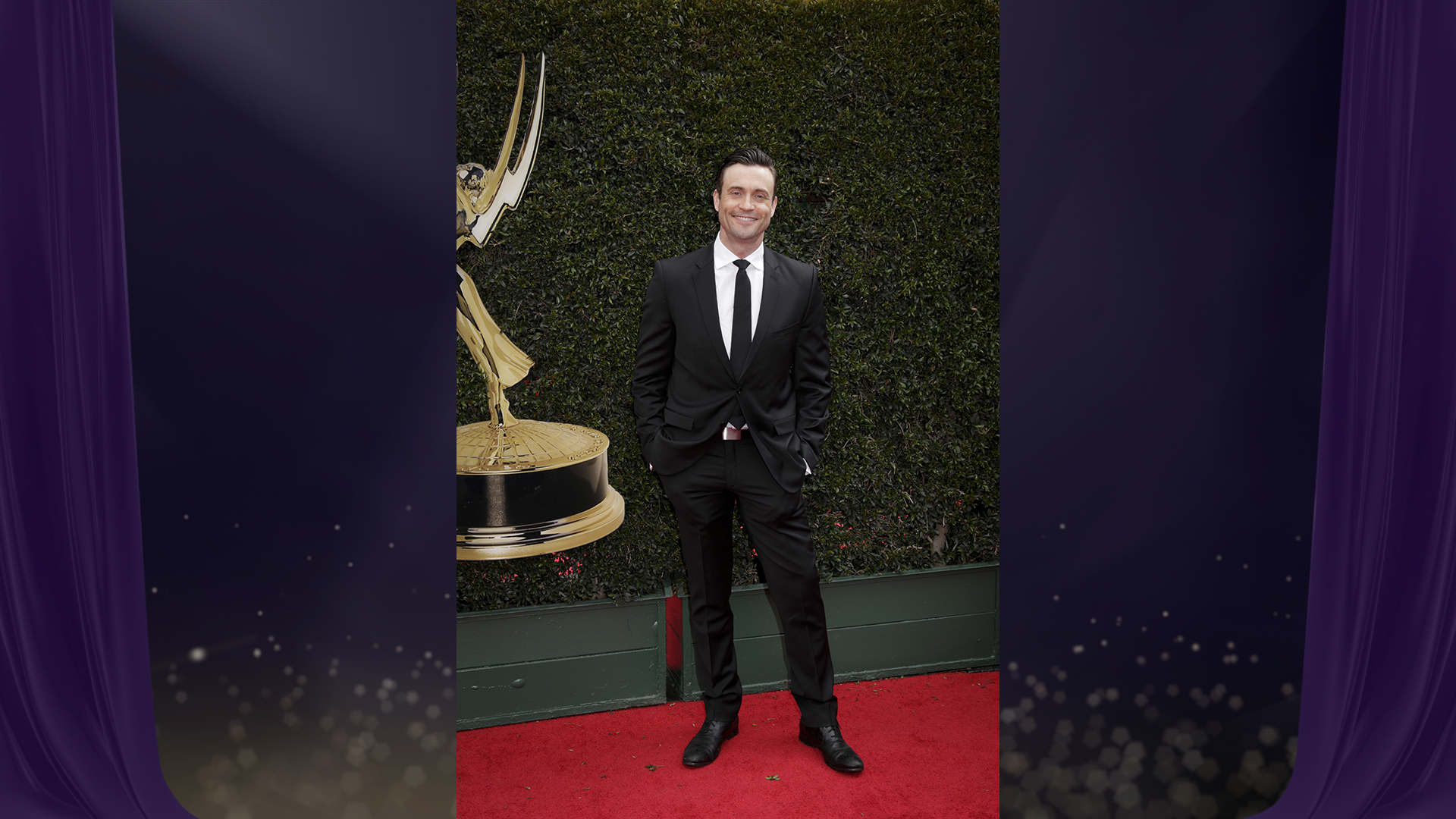 Daniel Goddard from The Young and the Restless shows off his shiny silver belt buckle while posing on the red carpet.