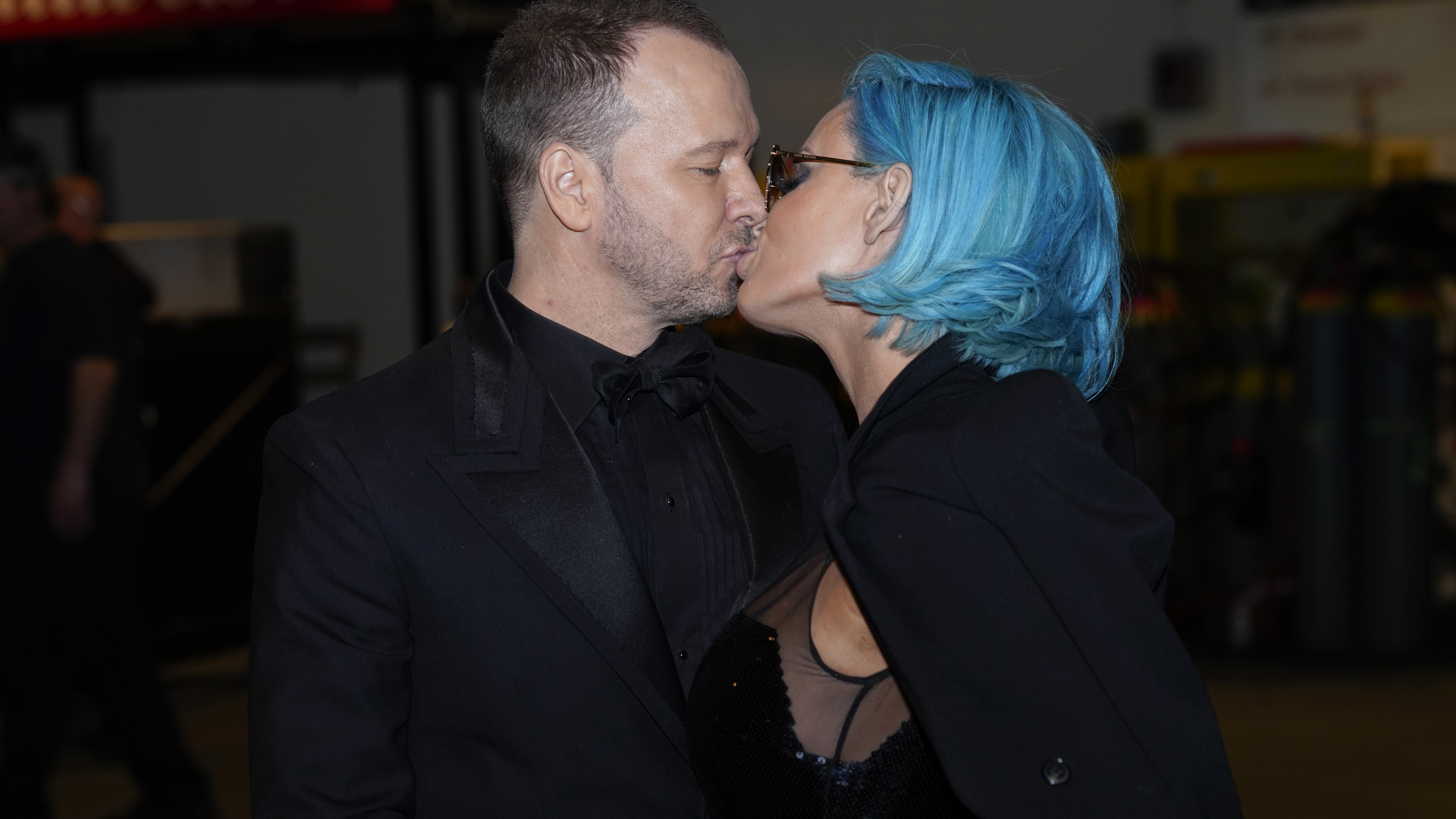 Blue Bloods star Donnie Wahlberg kisses his wife, Jenny McCarthy, backstage at the 60th Annual GRAMMY Awards.