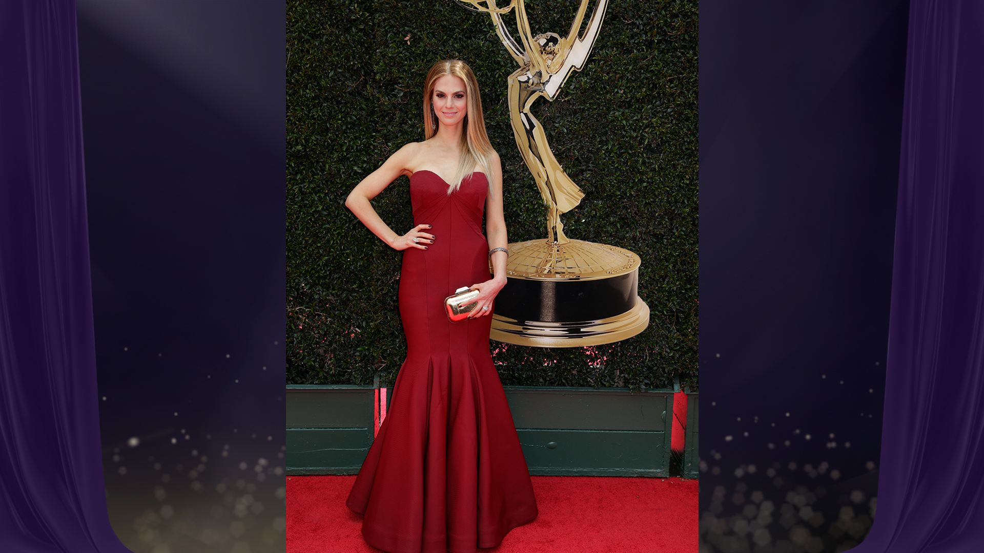CBS Daytime star Kelly Kruger poses in a red strapless trumpet dress with a shiny gold clutch.