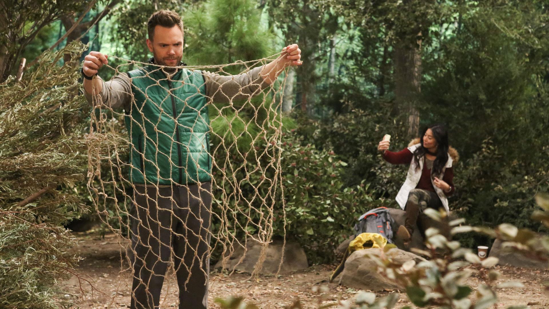 Jack untangles a net while Emma takes a selfie.
