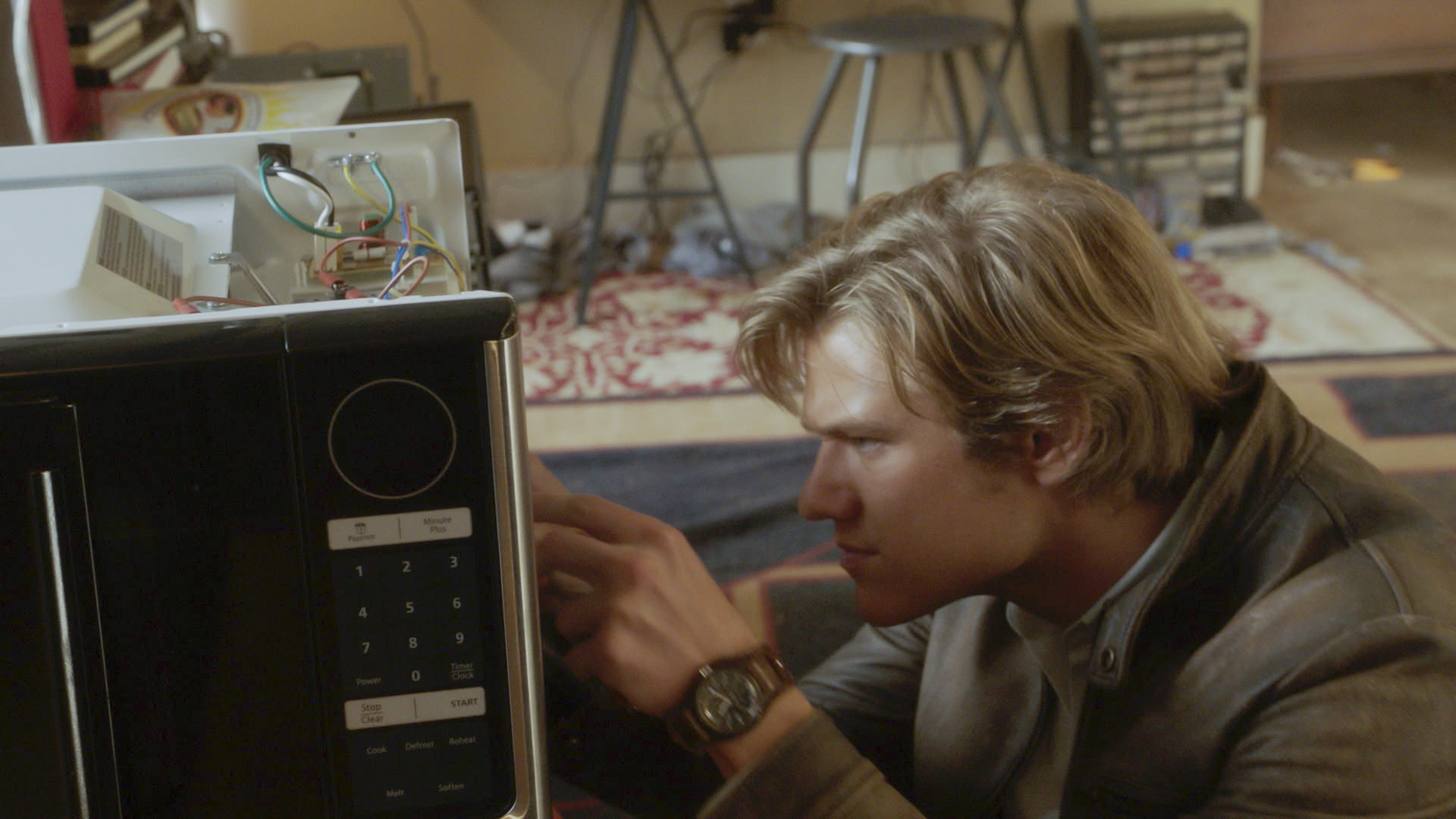 MacGyver dives into a microwave's electronics.