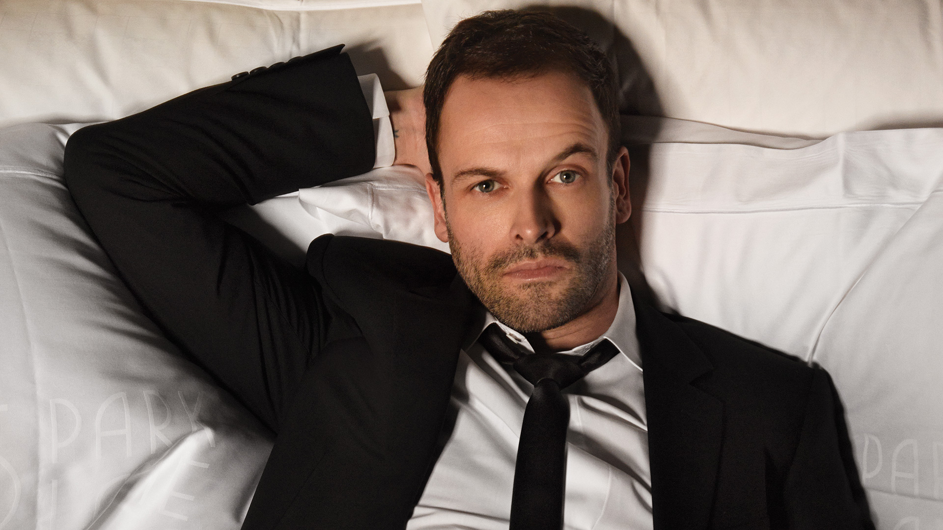 Jonny Lee Miller stretches out in bed