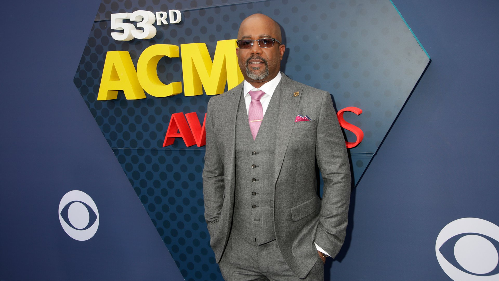 Darius Rucker accents his crisp gray suit with a pink tie and matching pocket square.