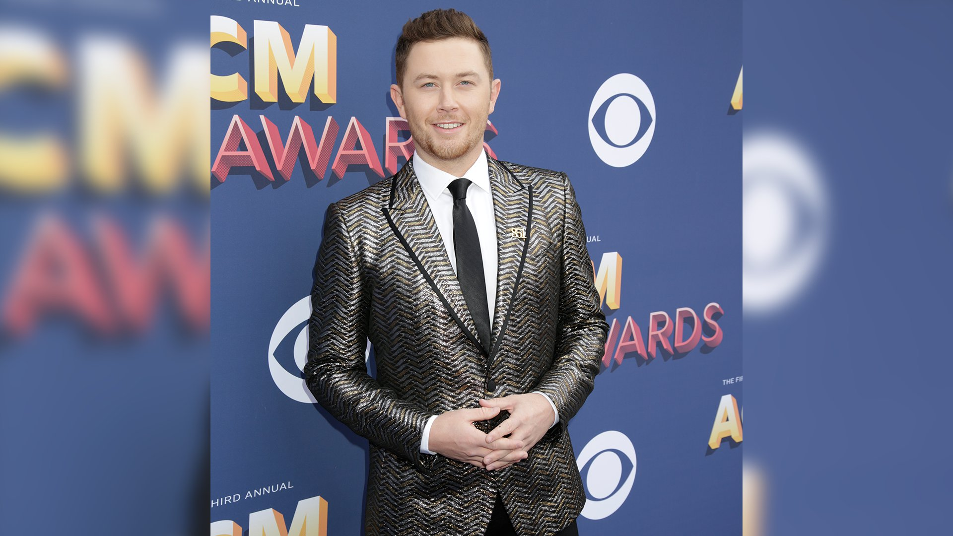Singer Scotty McCreery looks all grown up in his gold herringbone jacket and black-piped lapel.
