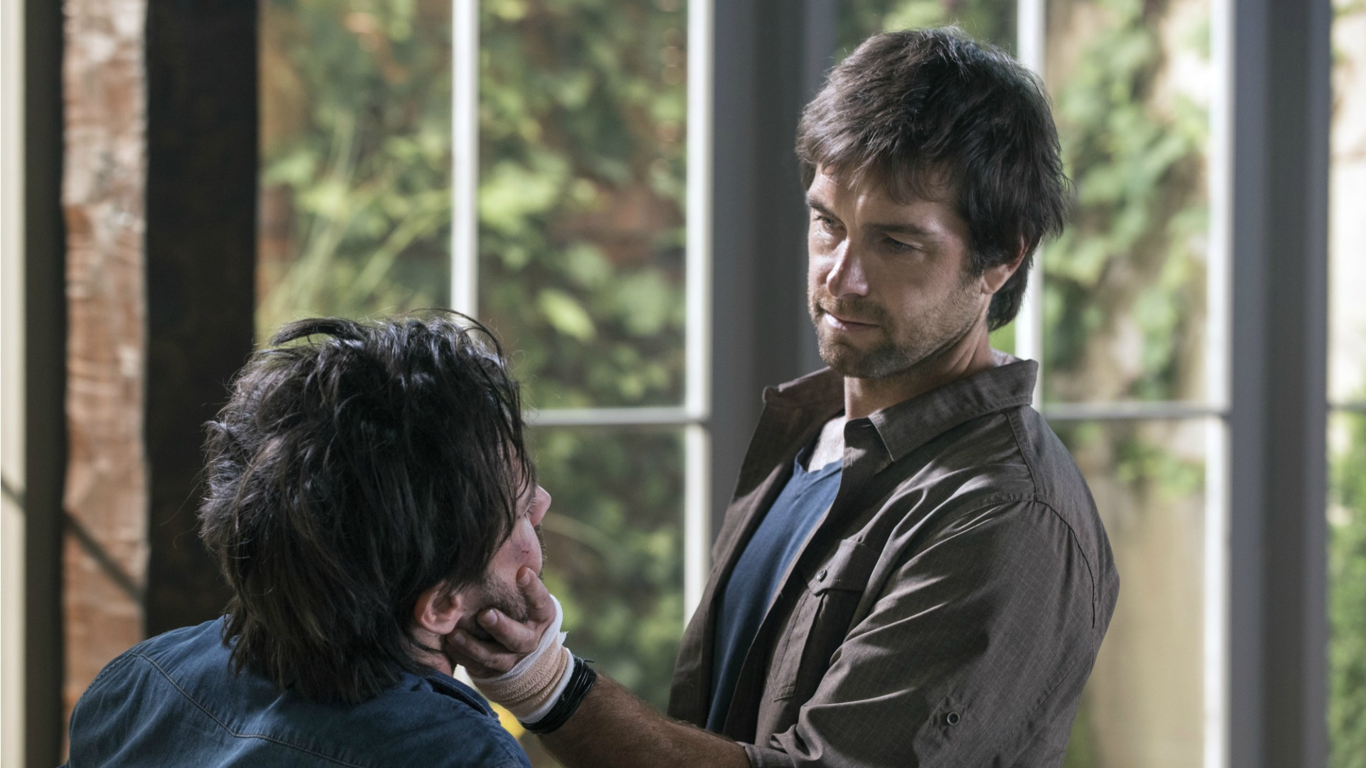Garrett inspects Cam's face.