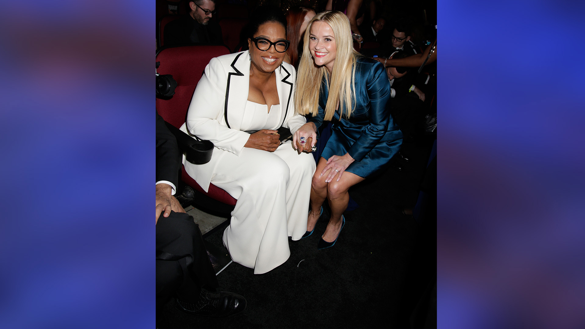Emmy presenters Oprah Winfrey and Reese Witherspoon hold hands in the crowd.