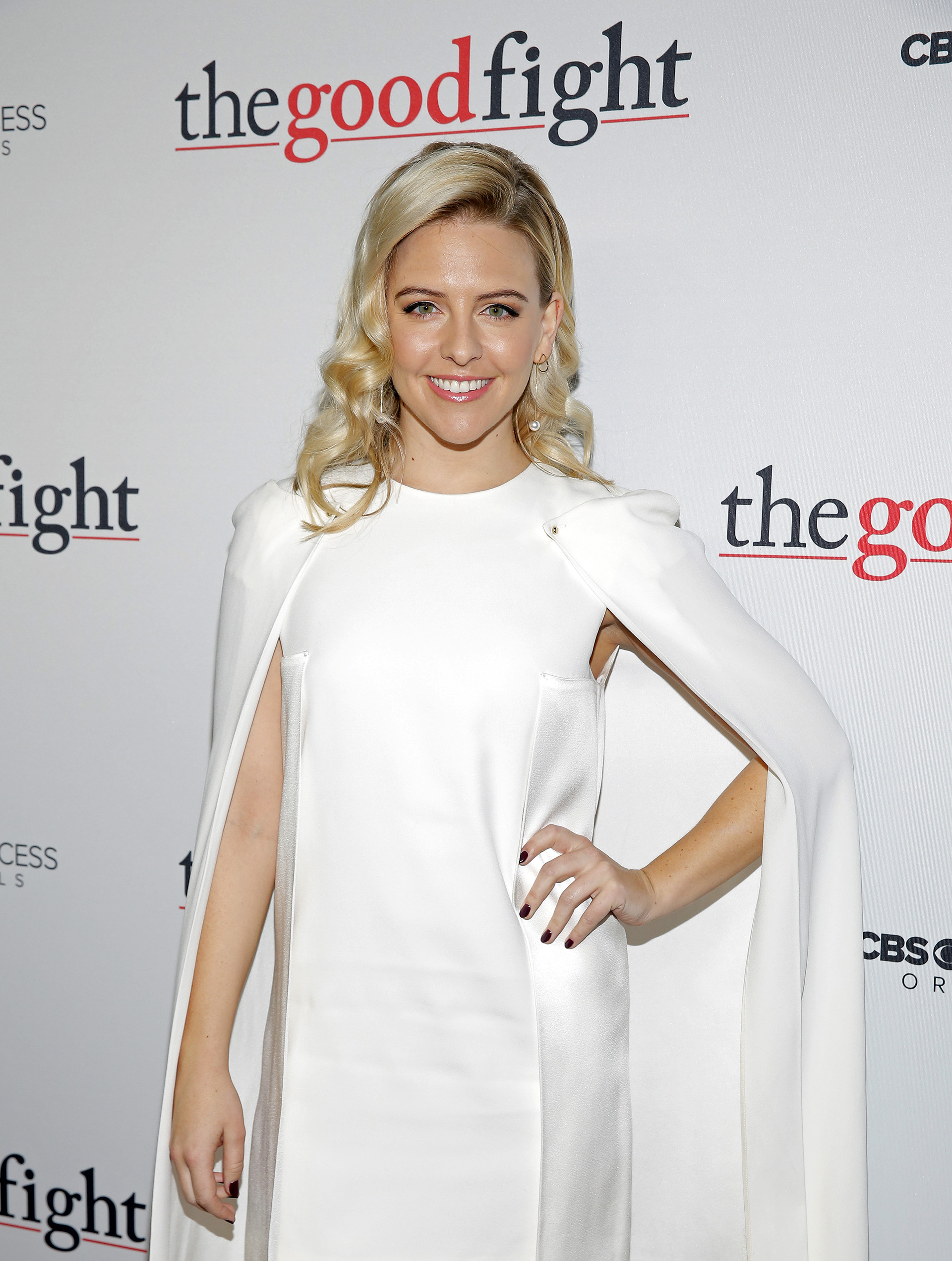 Helene Yorke glows in a white sheath dress featuring a sleek matching cape.