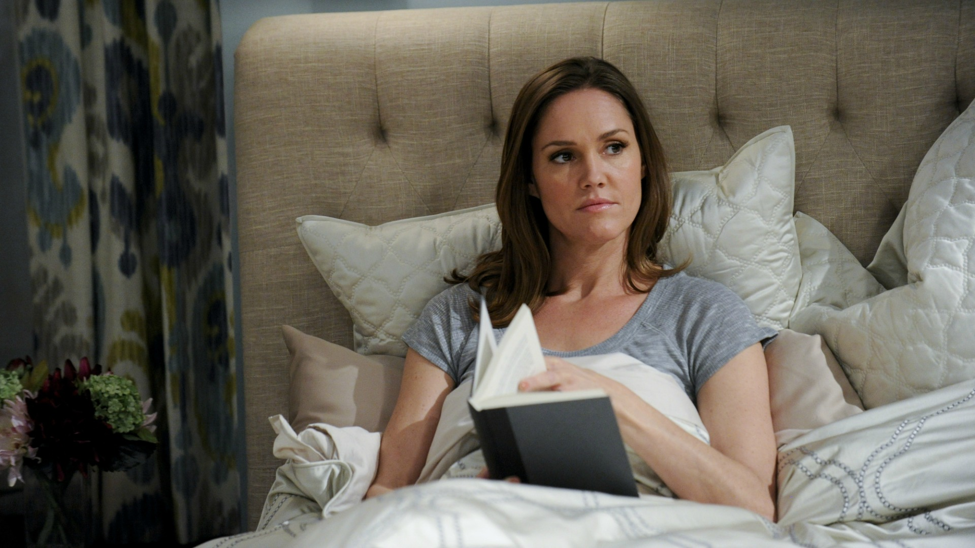 Donna reads a book in bed.