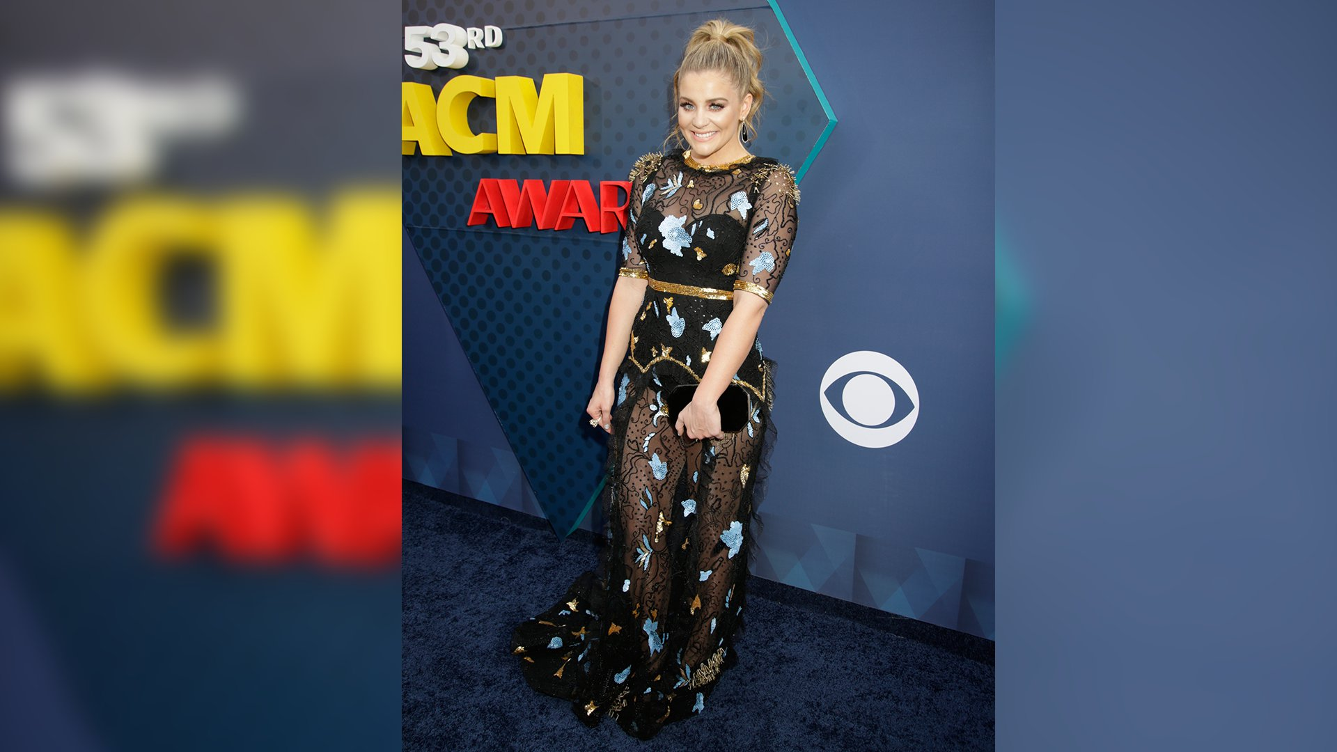 New Female Vocalist of the Year winner Lauren Alaina wears a high ponytail and heavenly black gown with floral appliqués.