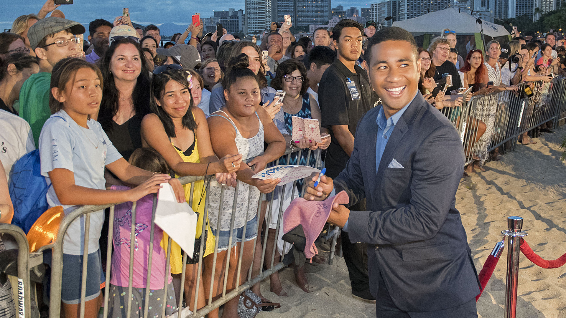Beulah Koale turns to smile as he signs autographs for fans on the red carpet.
