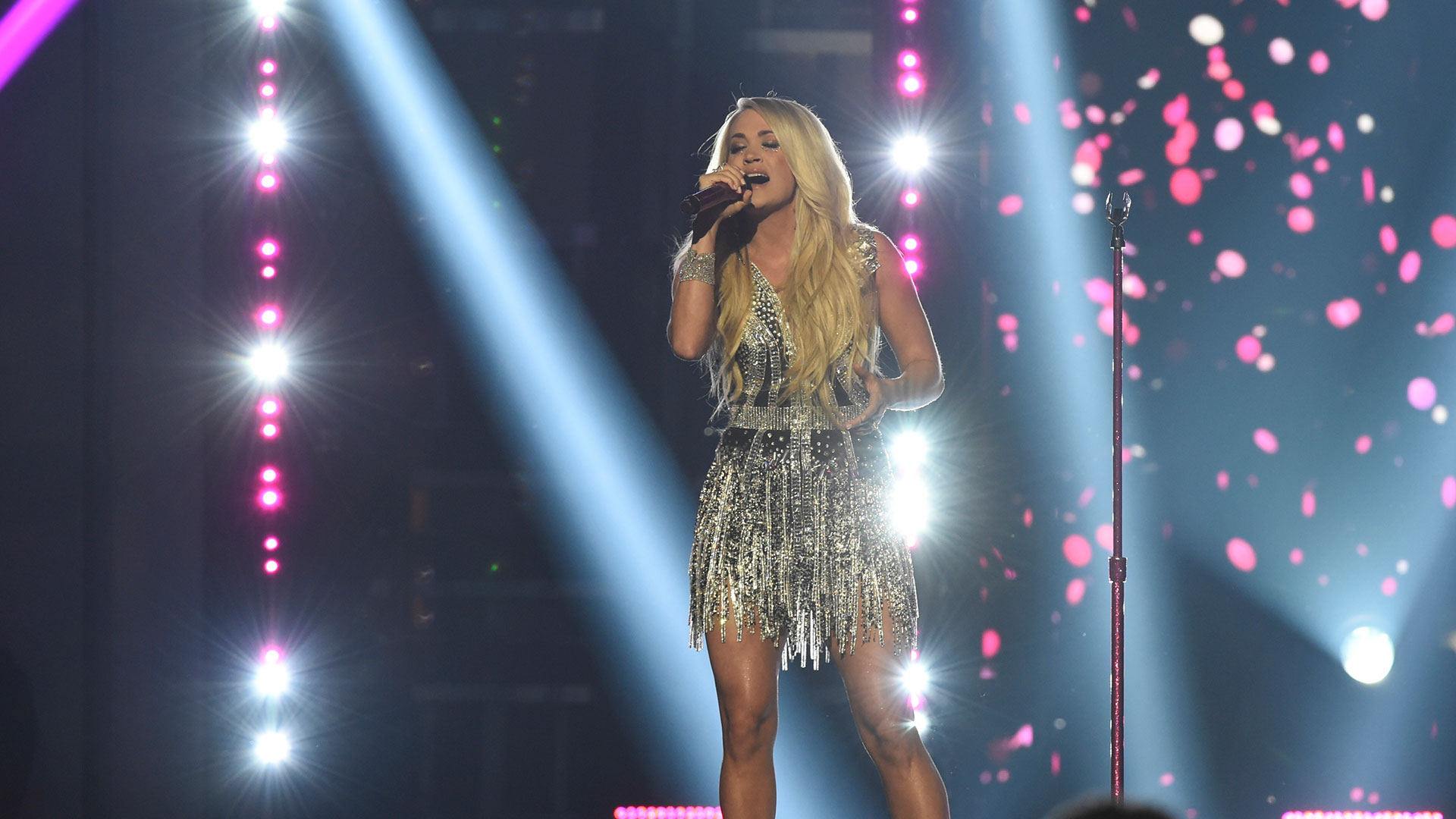 Sparkling in a silver mini-dress, Carrie Underwood performs her brand-new single,