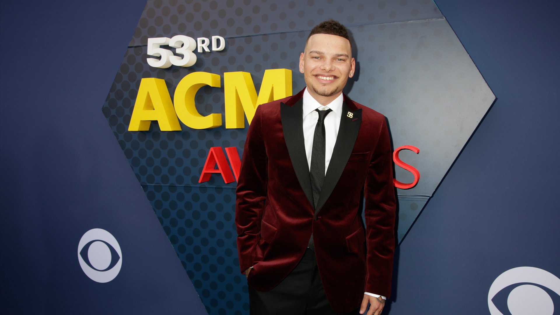 Kane Brown can't stop smiling while wearing a lush velvet blazer on the ACM red carpet.
