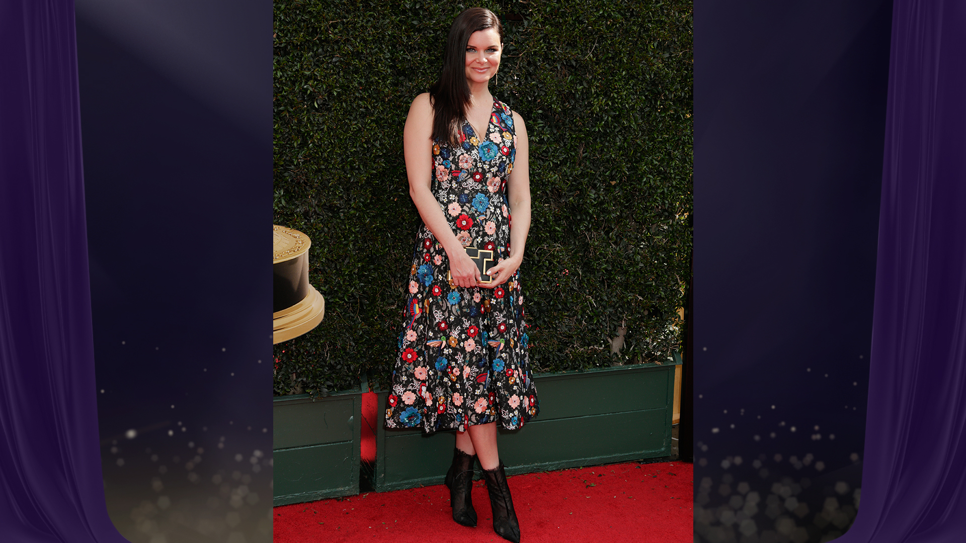 Heather Tom from The Bold and the Beautiful opts for a V-neck, tea-length black dress covered with floral appliqués.