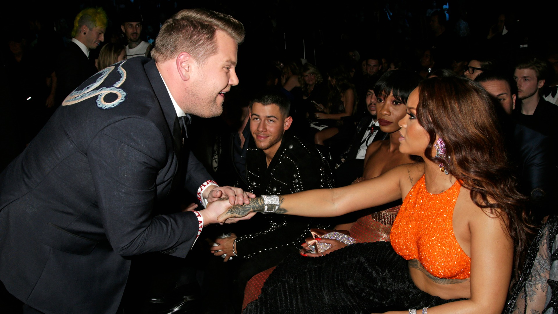 James Corden graciously reaches out for Rihanna's hand during a break in GRAMMY hosting duties.