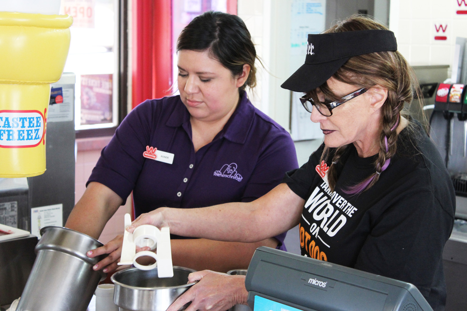 Cynthia learns a few things from Rhondelise, a fellow Weinerschnitzel employee, at the Amarillo, Texas location.