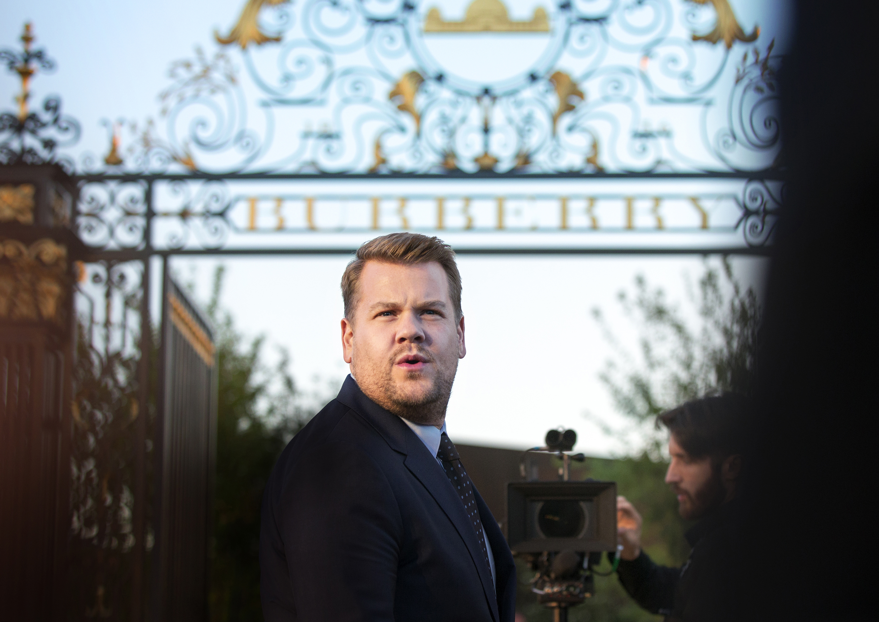 James Corden arrives outside the Burberry pearly gates.