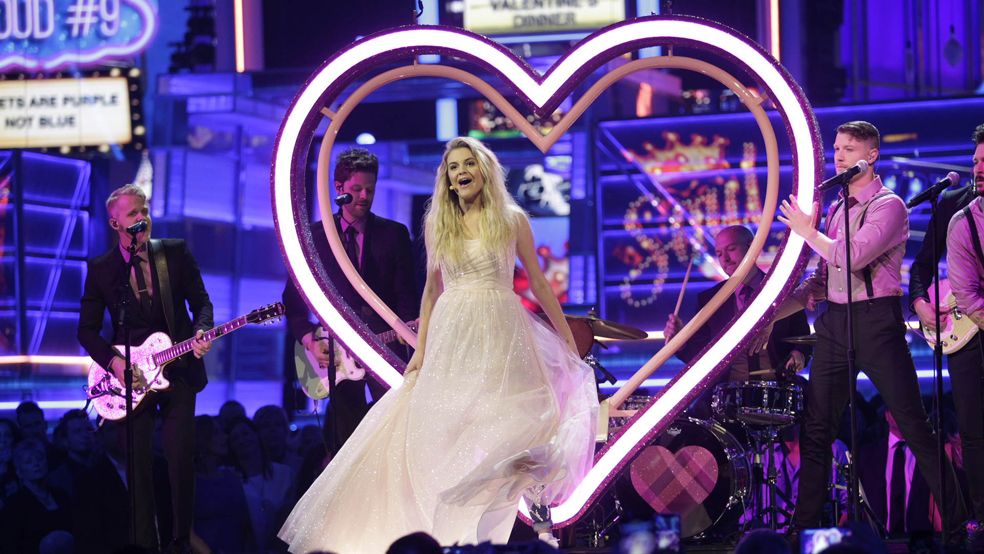 Dropping down in a neon heart, a shimmering Kelsea Ballerini performs