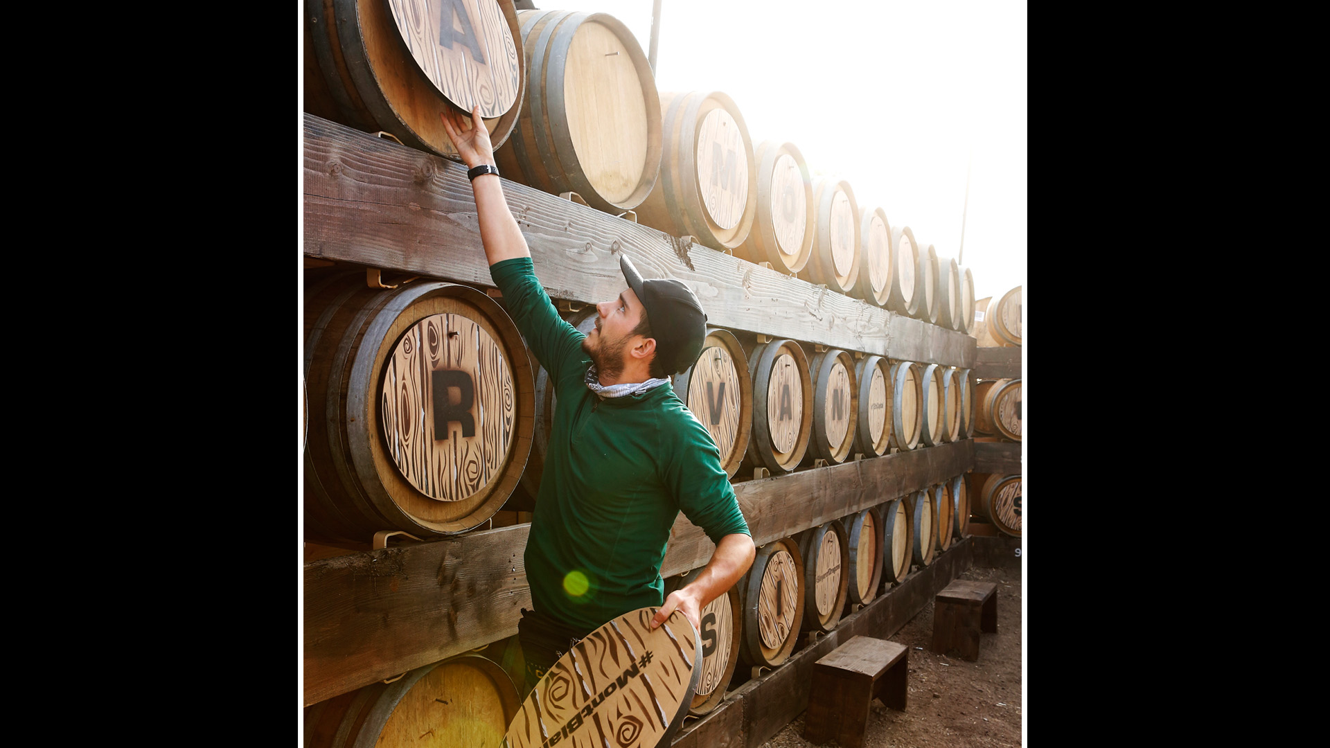 Korey grabs letters from the top of different wooden barrels.