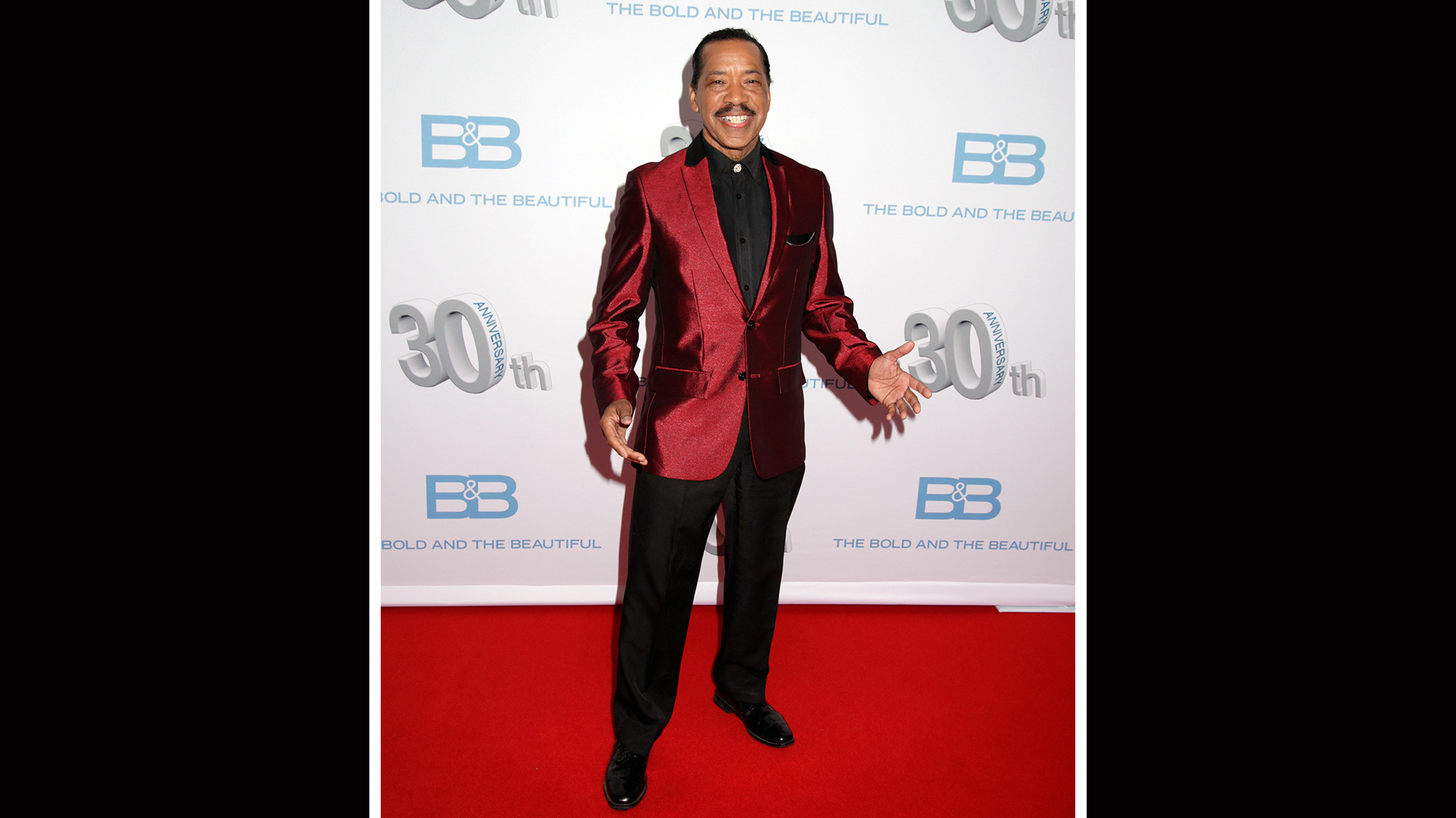 Obba Babatundé makes a bold statement in a sleek burgundy sports coat.