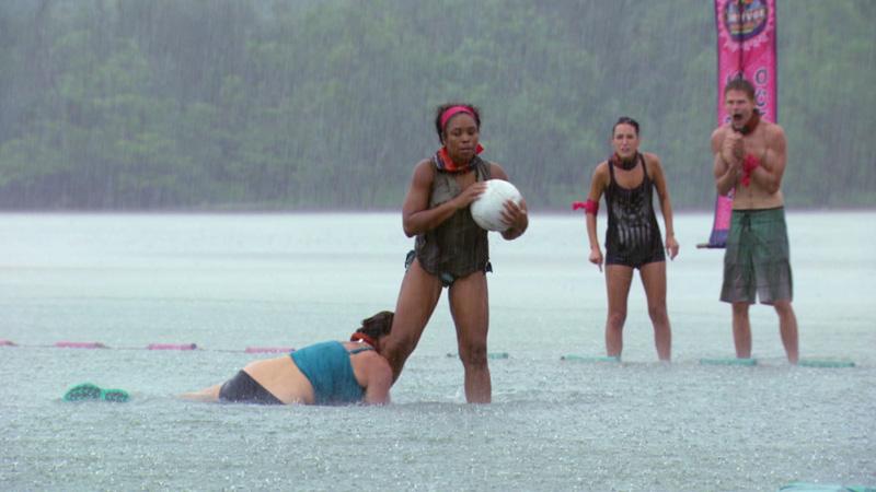 Kimmi grabs onto Tasha as she carries a ball tight toward the net.