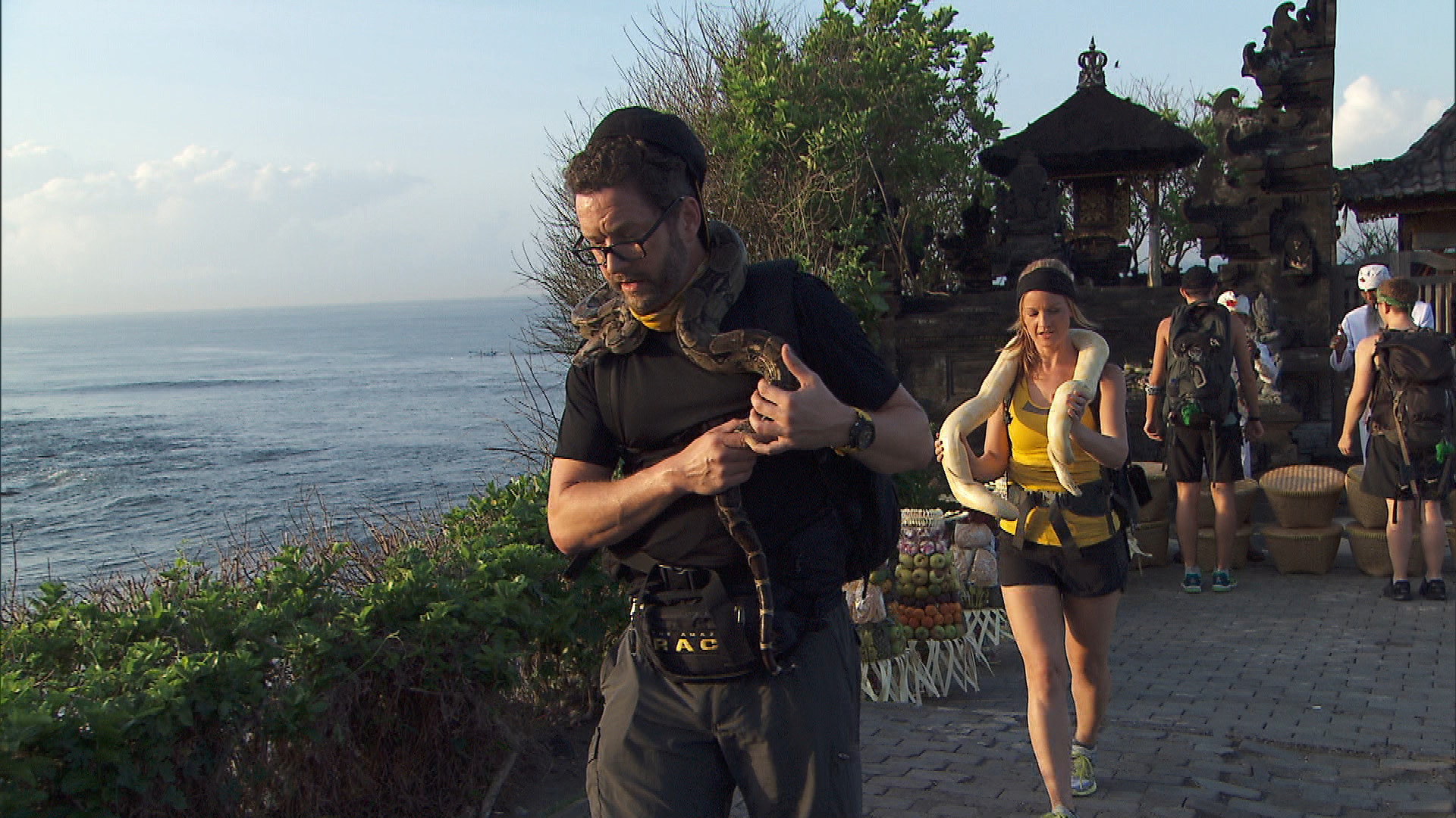 Burnie and Ashley try to move quickly while donning snakes around their necks.