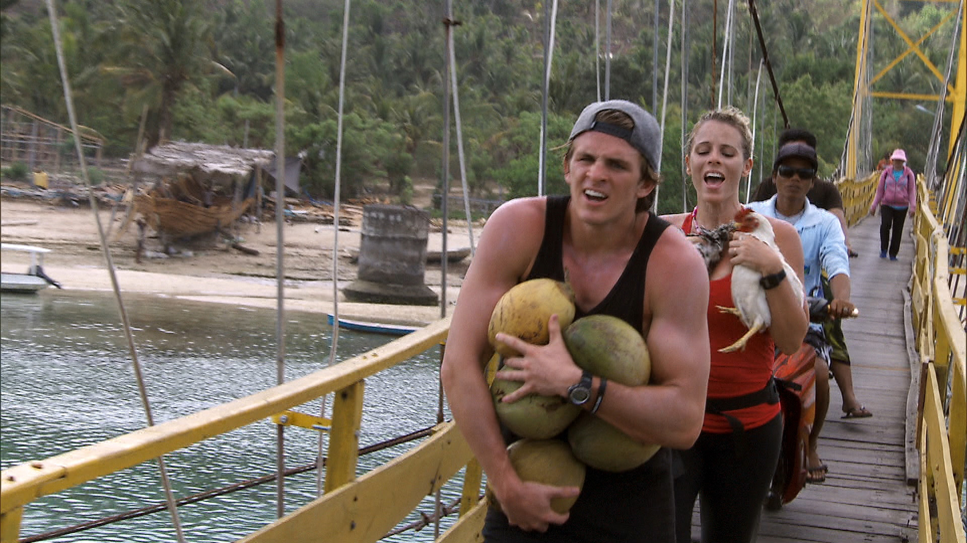 Cole and Sheri run across the bridge, carrying chickens and coconuts, to the Cenigan side.