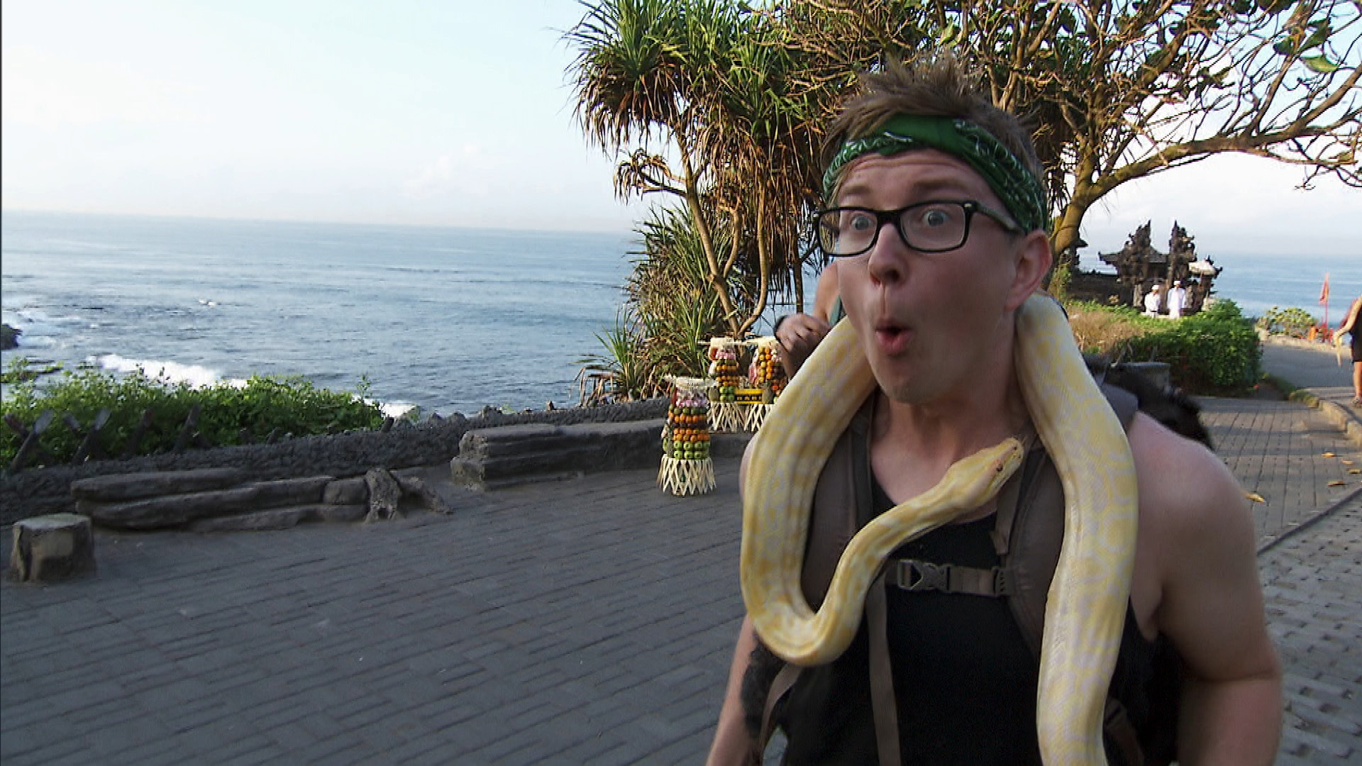 Tyler nervously wears a snake while walking to the monks at the Route Marker.