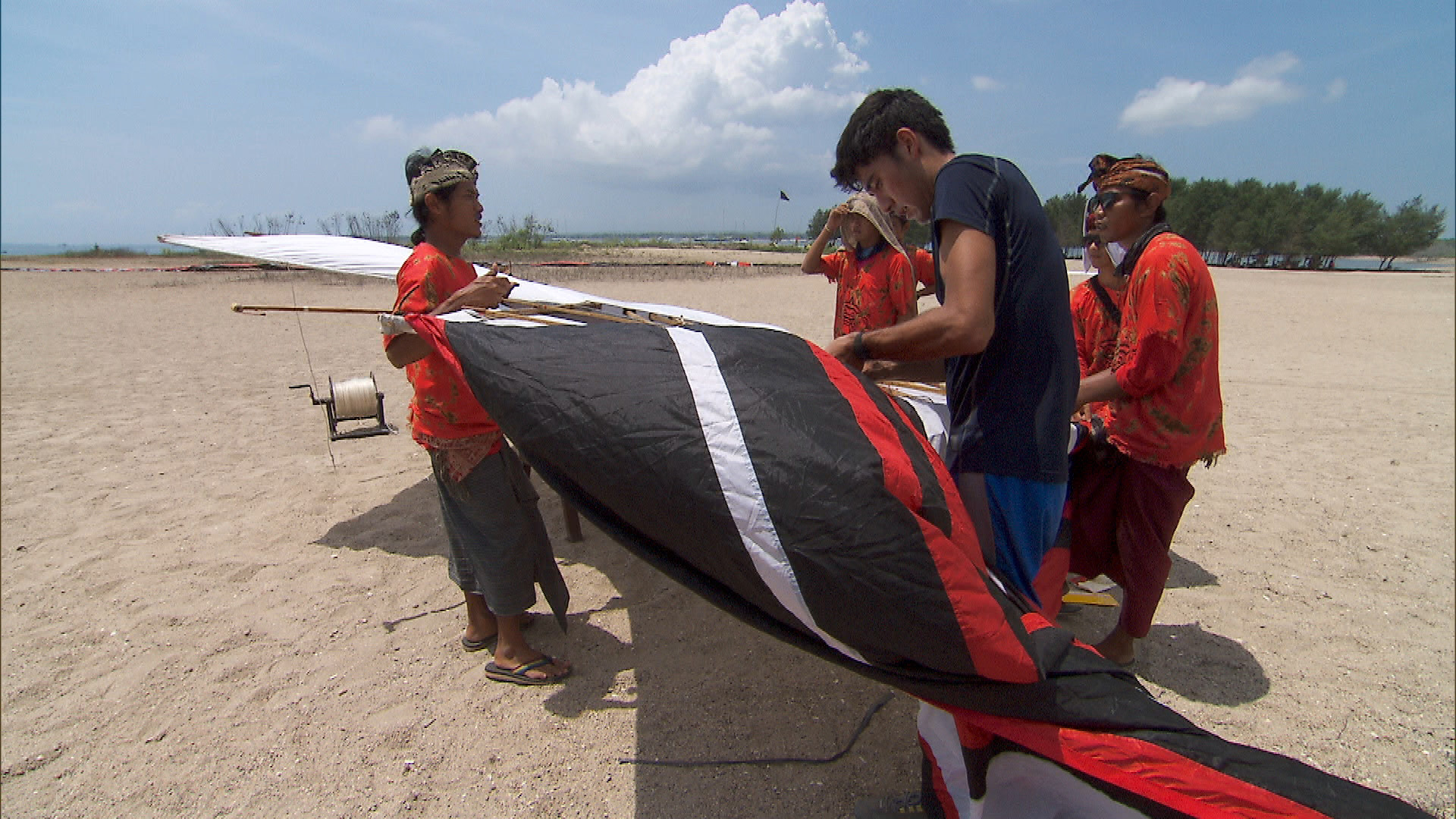 At the second Roadblock, Zach tries to help build and successfully fly a kite.
