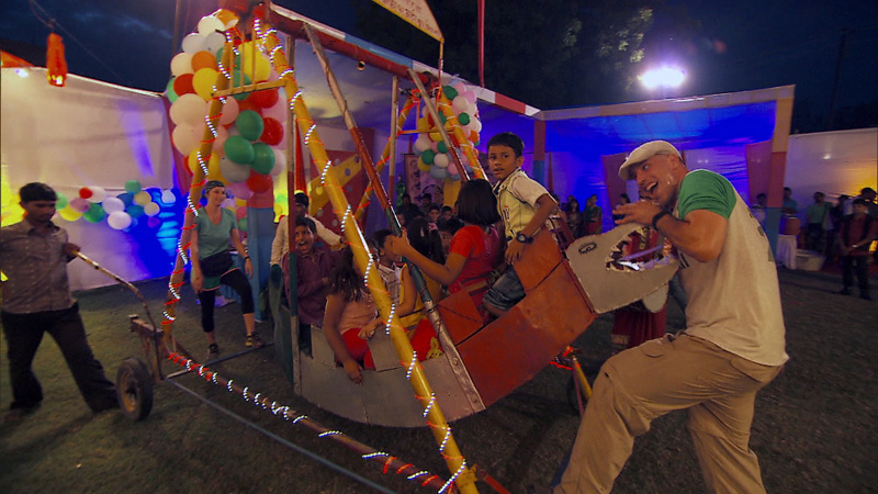 Justin and Diana deliver a homemade carnival swing and give the local children a ride.