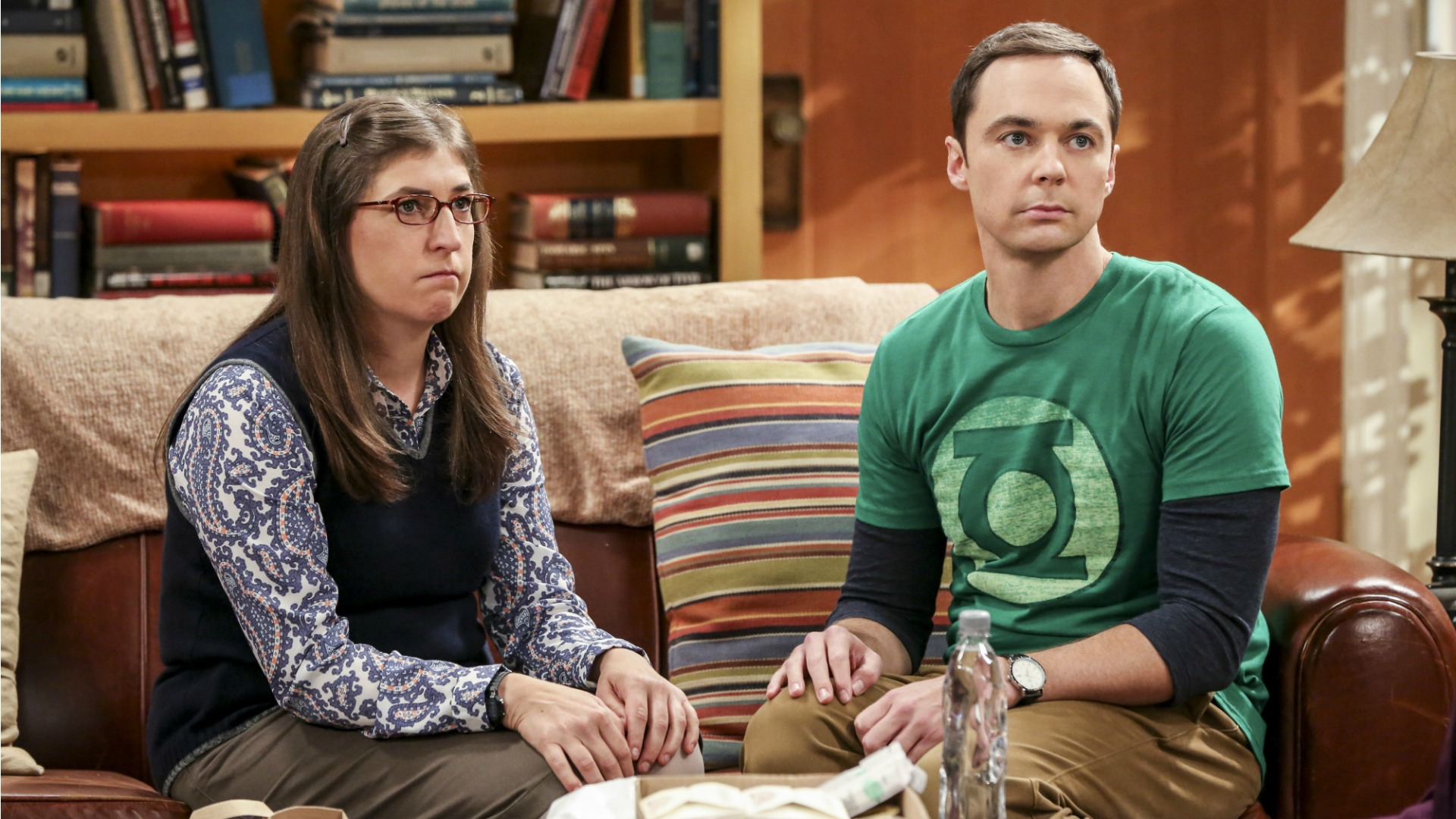 Amy and Sheldon look concerned on the couch.